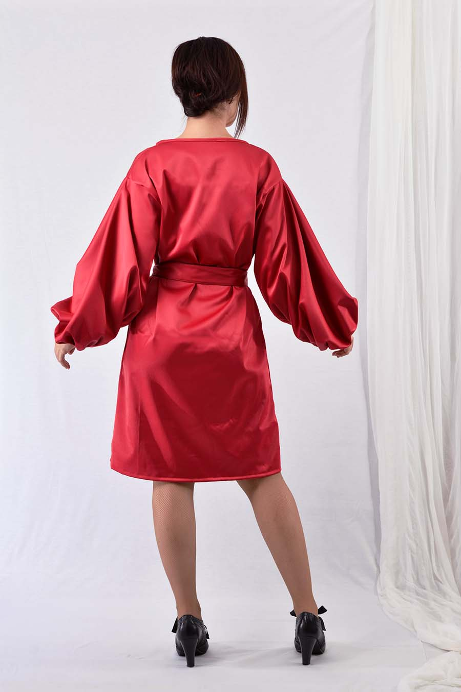 Red satin dress with puffy sleeves and belt from back
